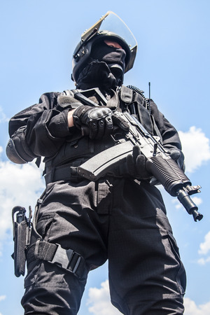 Spec ops soldier in black uniform and face mask with his rifle photo
