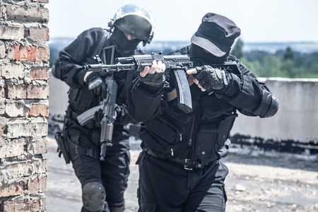 Two spec ops soldiers in black uniform in action Foto de archivo