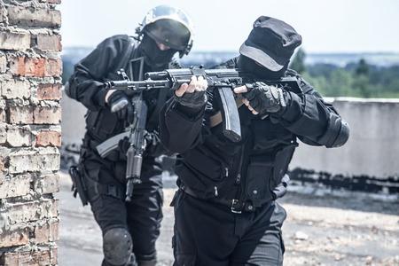 Two spec ops soldiers in black uniform in action Archivio Fotografico