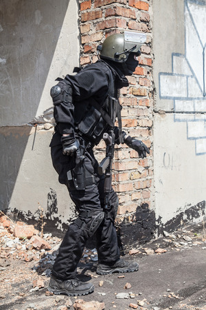 counter terrorism: Spec ops soldier in black uniform and face mask aiming his pistol Stock Photo