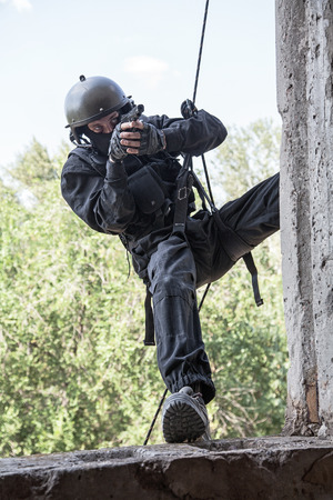 Spec ops soldier in face mask during rope exercises with weapons