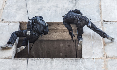rappelling: Spec ops soldier in face mask during rope exercises with weapons