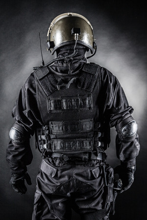 Spec ops soldier on black background shot from behind photo