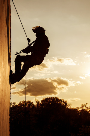 police equipment: Silhouette of police officer during rope exercises with weapons