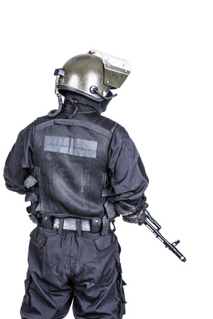 police equipment: Spec ops soldier in black uniform and face mask shot from behind Stock Photo