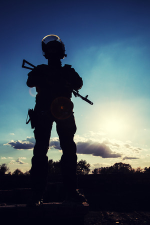 police equipment: Silhouette of police officer with weapons at sunset