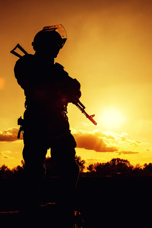 swat: Silhouette of police officer with weapons at sunset