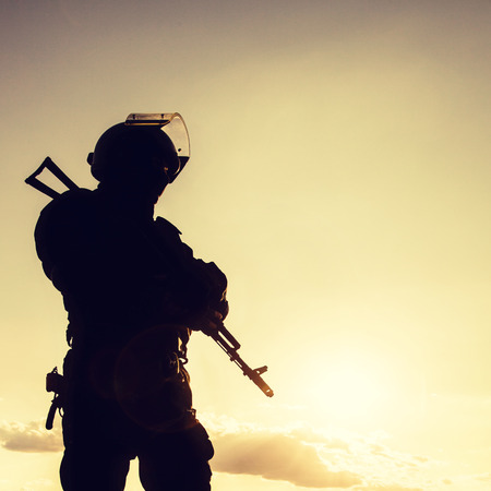 military special forces: Silhouette of police officer with weapons at sunset