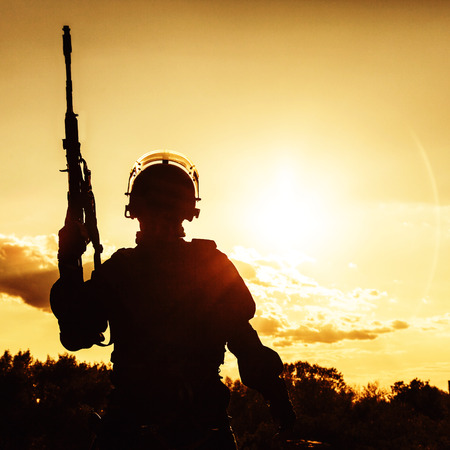 Silhouette of police officer with weapons at sunset photo