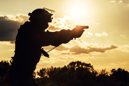 police equipment: Silhouette of police officer with pistol at sunset Stock Photo