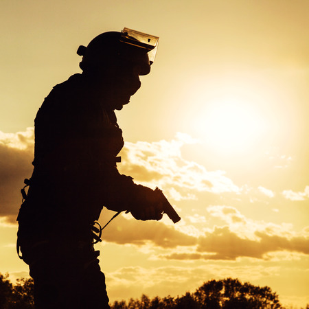 police helmet: Silhouette of police officer with pistol at sunset Stock Photo