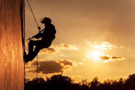 military forces: Silhouette of police officer during rope exercises with weapons