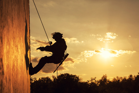 alpinist: Silhouette of police officer during rope exercises with weapons