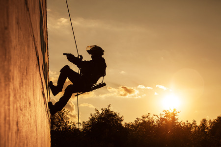 military special forces: Silhouette of police officer during rope exercises with weapons