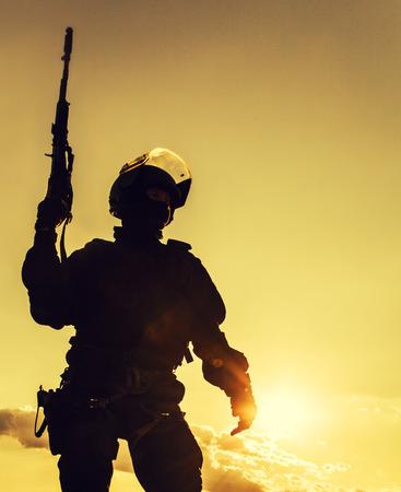 silhouette soldat: Silhouette de policier avec des armes au coucher du soleil