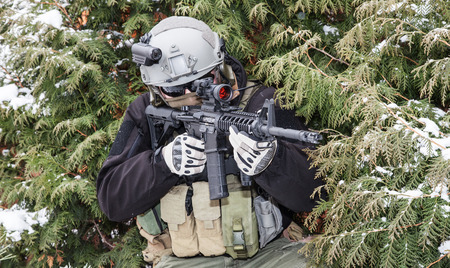 private security: Private military contractor PMC with assault rifle in the winter forest