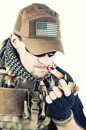 private security: Studio shot of private military contractor PMC smoking a cigar Stock Photo