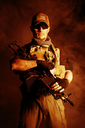 military forces: Private military contractor PMC with assault rifle on dark background