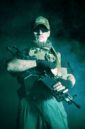 private security: Private military contractor PMC with assault rifle on dark background