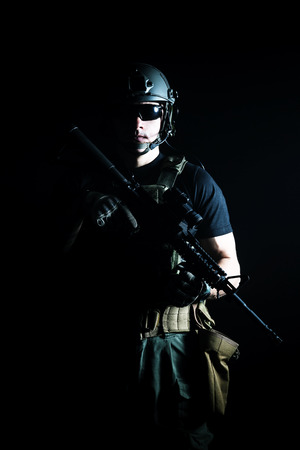 special agent: Private military contractor PMC with assault rifle on dark background