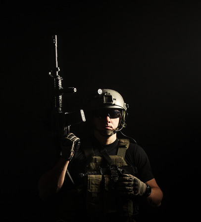 Private military contractor PMC with assault rifle on dark background photo