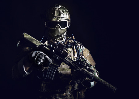 Special forces soldier with rifle on dark background