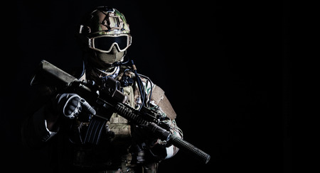 military uniform: Special forces soldier with rifle on dark background