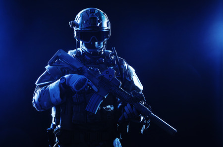 Special forces soldier with rifle on dark background photo