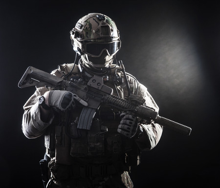 assault forces: Special forces soldier with rifle on dark background