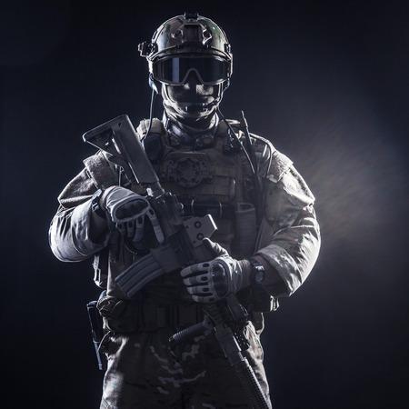 soldado: Soldado de las fuerzas especiales con el rifle en el fondo oscuro