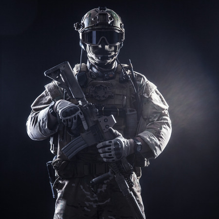 armour: Special forces soldier with rifle on dark background