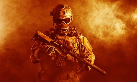 wojenne: Siły specjalne żołnierz z karabinem w ogniu