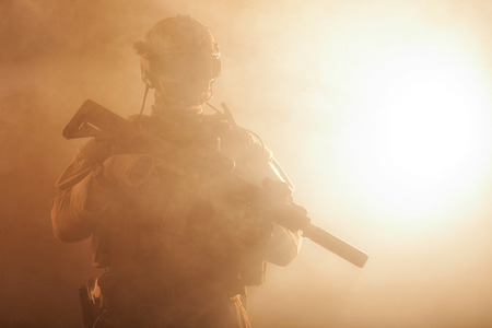 Special forces soldier with rifle in the smoke