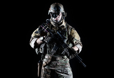 United States Army ranger with assault rifle on dark background