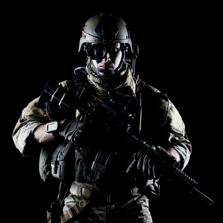 military special forces: United States Army ranger with assault rifle on dark background