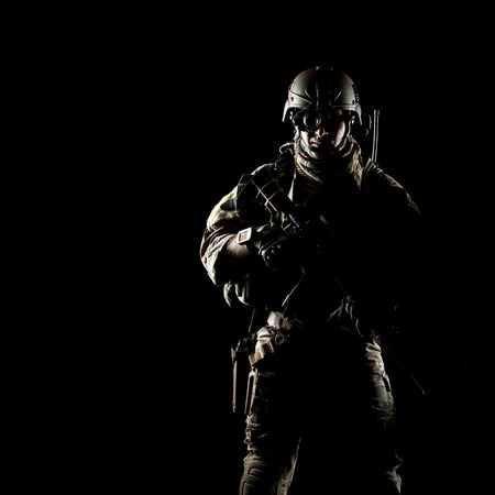 United States Army ranger with assault rifle on dark background photo