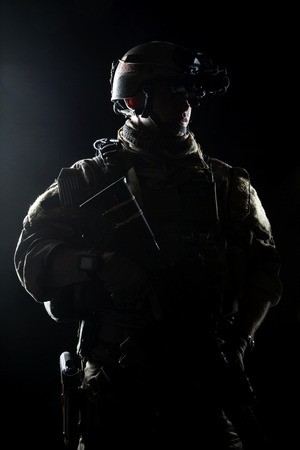 assault forces: United States Army ranger with assault rifle on dark background