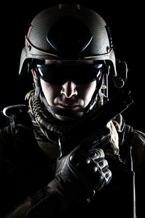 United States Army ranger with pistol on dark background