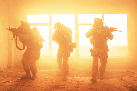 United States Army rangers during the military operation in the smoke and fire Imagens