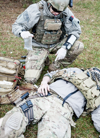 United States Army ranger treating the wounds of his injured fellow in arms Stock Photo