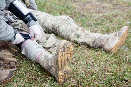 battle: United States Army ranger treating the wounds of his injured fellow in arms Stock Photo