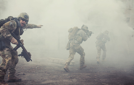 military uniform: United States Army rangers during the military operation in the smoke and fire Stock Photo