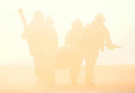military special forces: Squad of soldier evacuate the injured fellow in arms hiding in the smoke