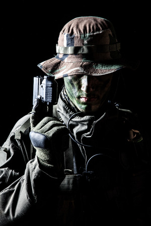 military special forces: Jagdkommando soldier Austrian special forces with pistol on dark background