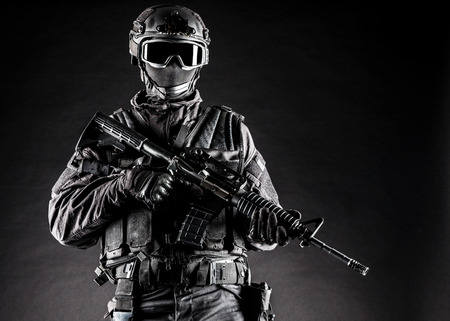 Spec ops police officer SWAT in black uniform and face mask Stock Photo