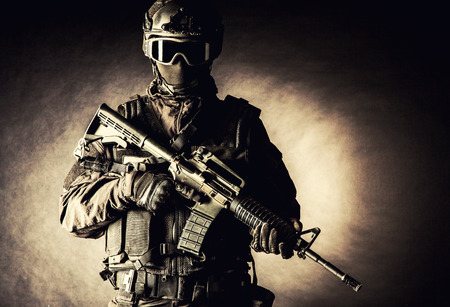 Spec ops police officer SWAT in black uniform and face mask 스톡 콘텐츠