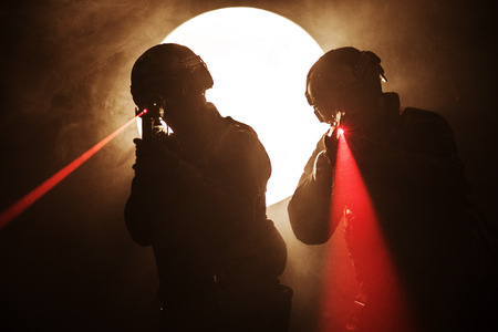 Spec ops police officers SWAT in the smoke and fire with laser sights
