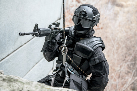 Spec ops police officer SWAT during rope exercises with weapons Stock Photo