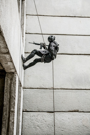 counter terrorism: Spec ops police officer SWAT during rope exercises with weapons Stock Photo