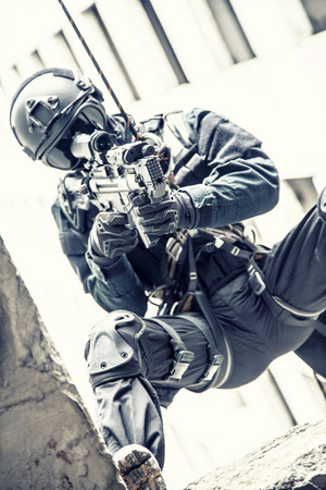 rappelling: Spec ops police officer SWAT during rope exercises with weapons Stock Photo